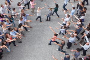 People extending arms to each other in crowd